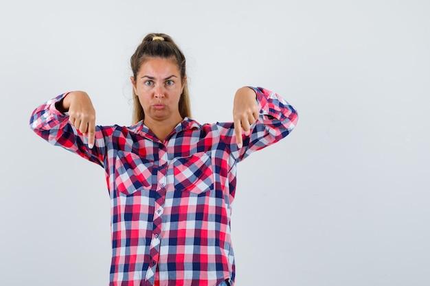 Jonge dame in geruit overhemd die naar beneden wijst en bezorgd, vooraanzicht kijkt.