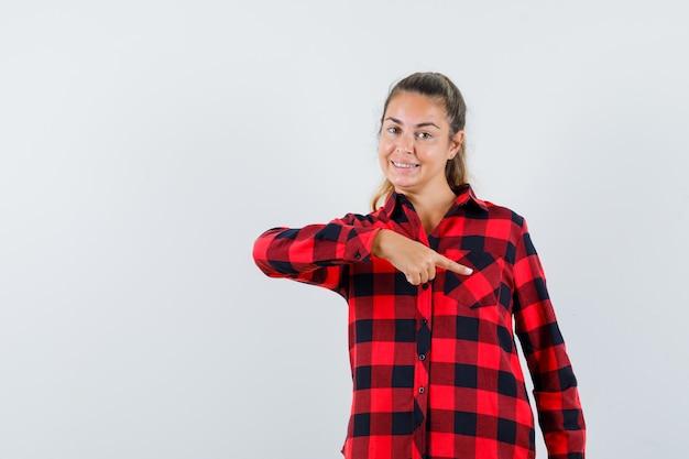 Jonge dame in geruit overhemd die naar beneden wijst en vrolijk kijkt