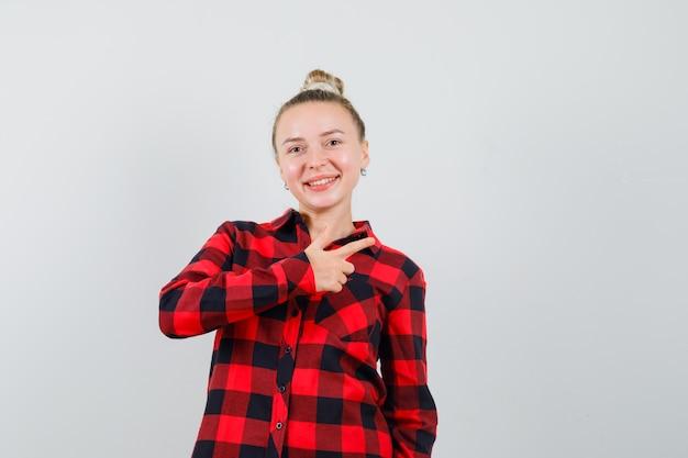 Jonge dame in geruit overhemd die naar de kant wijst en vrolijk kijkt