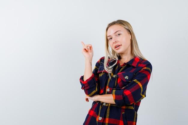 Jonge dame in geruit overhemd die omhoog wijst en gelukkig, vooraanzicht kijkt.