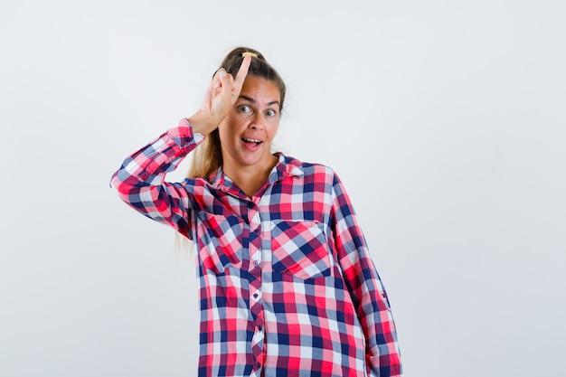 Jonge dame in geruit overhemd die omhoog wijst en vrolijk, vooraanzicht kijkt.