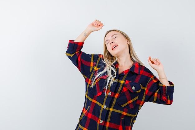 Jonge dame in geruit overhemd die winnaargebaar toont en gelukkig, vooraanzicht kijkt.