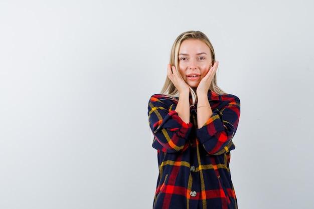 Jonge dame in geruit overhemd hand in hand op de wangen en kijkt gelukkig, vooraanzicht.