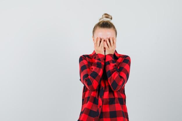 Jonge dame in geruit overhemd hand in hand op gezicht en op zoek triest