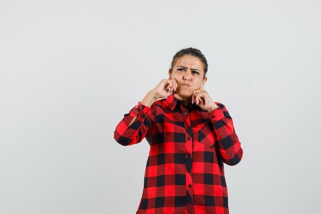 Jonge dame in geruit overhemd hand in hand op wangen blazen en peinzend kijken