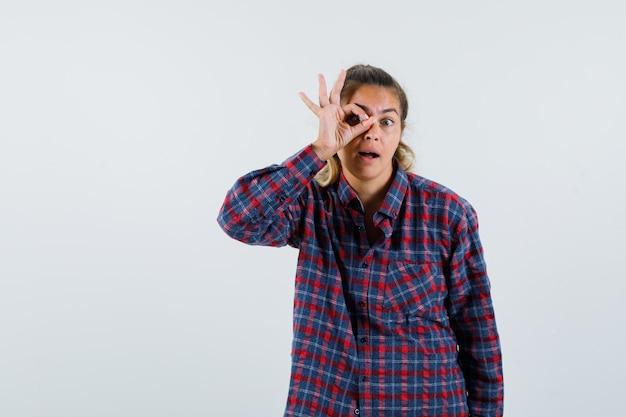 Jonge dame in geruit overhemd ok gebaar op oog tonen en nieuwsgierig, vooraanzicht kijken.