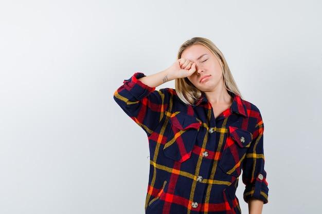 Jonge dame in geruit overhemd oog wrijven en op zoek slaperig, vooraanzicht.