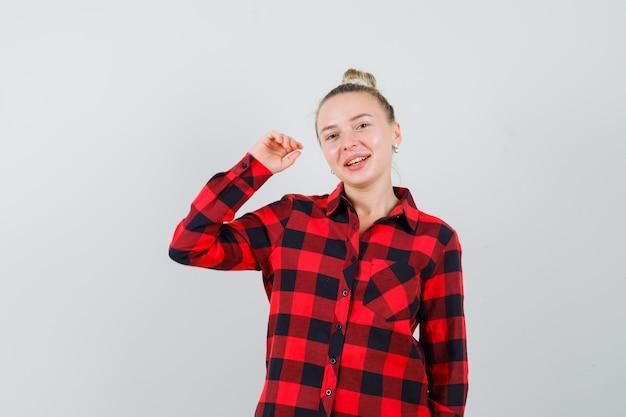 Jonge dame in geruit overhemd poseren terwijl het opheffen van de arm en er vrolijk uitziet