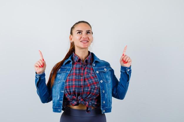 Jonge dame in geruit overhemd, spijkerjasje dat omhoog wijst en er vrolijk uitziet, vooraanzicht.