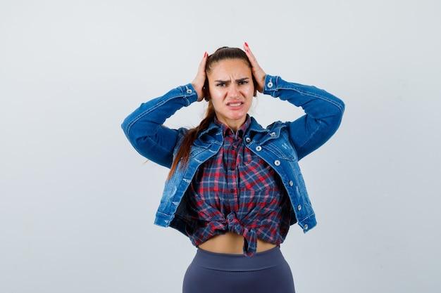 Jonge dame in geruit overhemd, spijkerjasje met handen op het hoofd en pijnlijk, vooraanzicht.
