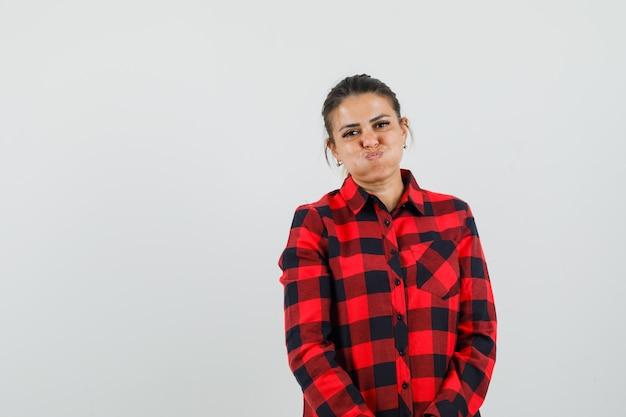 Jonge dame in geruit overhemd waait wangen en kijkt positief
