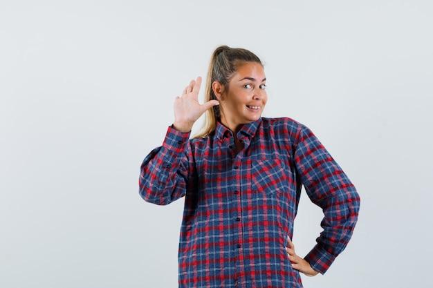 Jonge dame in geruit overhemd zwaaiende hand voor groet en op zoek gelukkig, vooraanzicht.