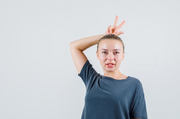 Jonge dame in grijs t-shirt met v-teken achter het hoofd als hoorns en ziet er grappig uit