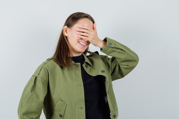 Jonge dame in groen jasje die hand op ogen houdt en opgewekt, vooraanzicht kijkt.