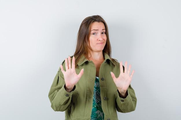 Jonge dame in groen jasje die weigeringsgebaar toont en terughoudend kijkt, vooraanzicht.