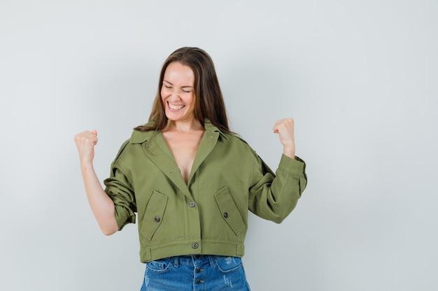 Jonge dame in groen jasje, korte broek die winnaargebaar toont en gelukkig, vooraanzicht kijkt.