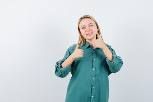 Jonge dame in groen overhemd die dubbele duimen toont en gelukkig kijkt
