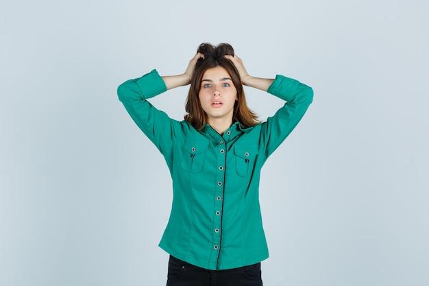 Jonge dame in groen overhemd hand in hand op het hoofd en kijkt verbijsterd, vooraanzicht.