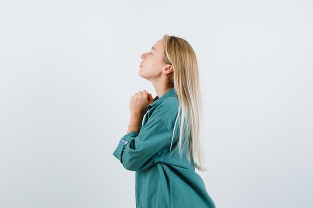 Jonge dame in groen shirt die handen vasthoudt in een biddend gebaar en er hoopvol uitziet.