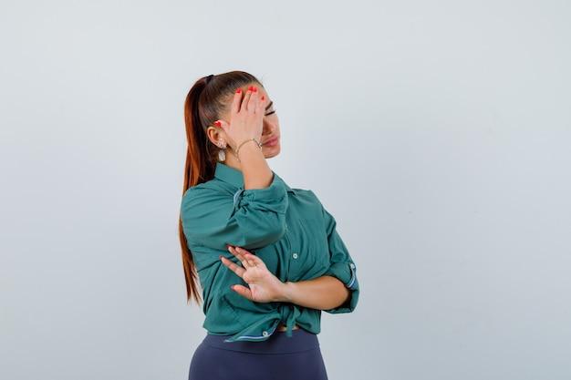 Jonge dame in groen shirt die lijdt aan hoofdpijn en er moe uitziet, vooraanzicht.