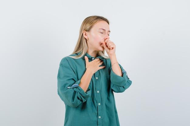 Jonge dame in groen shirt lijdt aan hoest en ziet er ziek uit