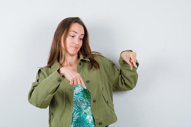 Jonge dame in groene jas die naar beneden wijst en er onzeker uitziet, vooraanzicht.