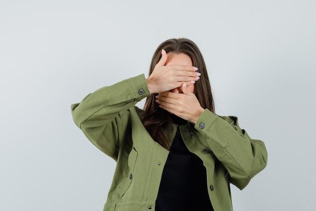 Jonge dame in groene jas hand in hand op haar mond en ogen en bang, vooraanzicht op zoek.
