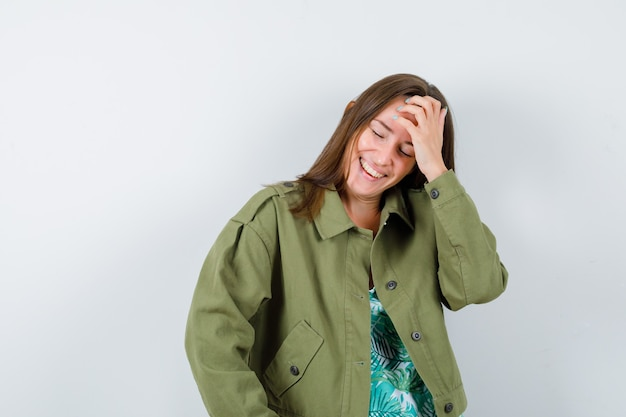 Jonge dame in groene jas met hand op het voorhoofd en ziet er gelukkig uit, vooraanzicht.
