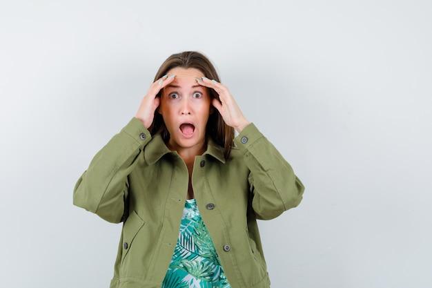 Jonge dame in groene jas met handen boven het hoofd en geschokt, vooraanzicht.