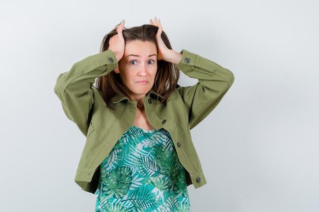 Jonge dame in groene jas met handen op het hoofd en perplex kijkend, vooraanzicht.