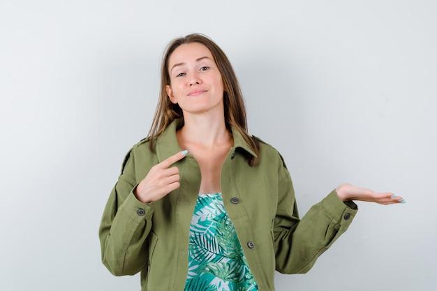 Jonge dame in groene jas wijzend naar de rechterbovenhoek, palm opzij spreidend en trots kijkend, vooraanzicht.