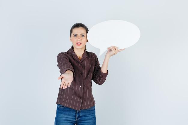 Jonge dame in hemd, jeans die de hand uitstrekt naar de camera, een papieren poster houdt en er ontevreden uitziet, vooraanzicht.