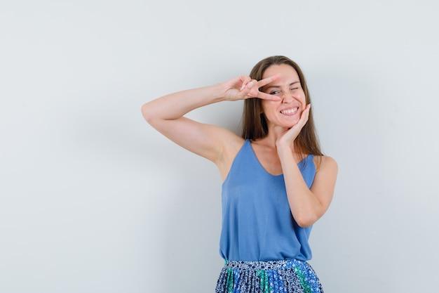Jonge dame in hemd, rok die overwinningsgebaar op oog toont en vrolijk, vooraanzicht kijkt.