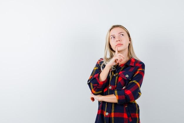 Jonge dame in het denken pose in geruit overhemd en besluiteloos op zoek. vooraanzicht.