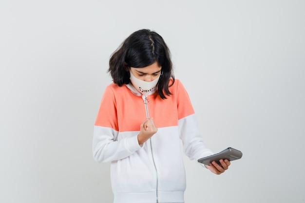 Jonge dame in hoodie, gezichtsmasker berekenen en gericht kijken