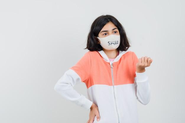 Jonge dame in hoodie, gezichtsmasker deelt haar mening en kijkt gefocust