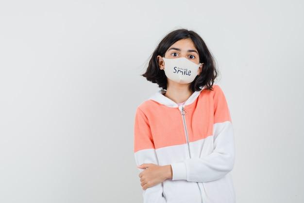 Jonge dame in hoodie, gezichtsmasker die haar arm met hand vasthoudt en verlegen kijkt