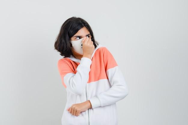 Jonge dame in hoodie, gezichtsmasker met vuist op haar mond en bang op zoek
