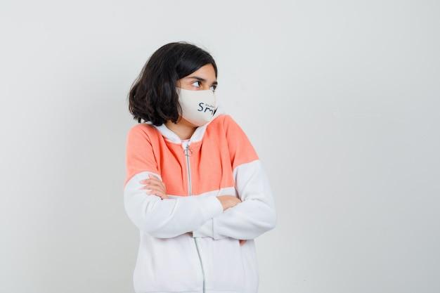 Jonge dame in hoodie, gezichtsmasker staat met gekruiste armen en kijkt boos