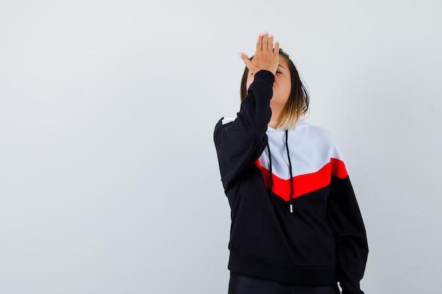 Jonge dame in hoodie-trui die hand op het voorhoofd houdt en er moe uitziet
