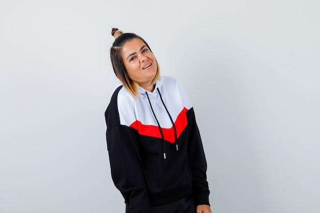 Jonge dame in hoodie-trui die naar de camera kijkt en er vrolijk uitziet