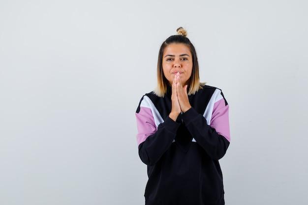 Jonge dame in hoodie trui hand in hand in biddend gebaar en hoopvol kijken