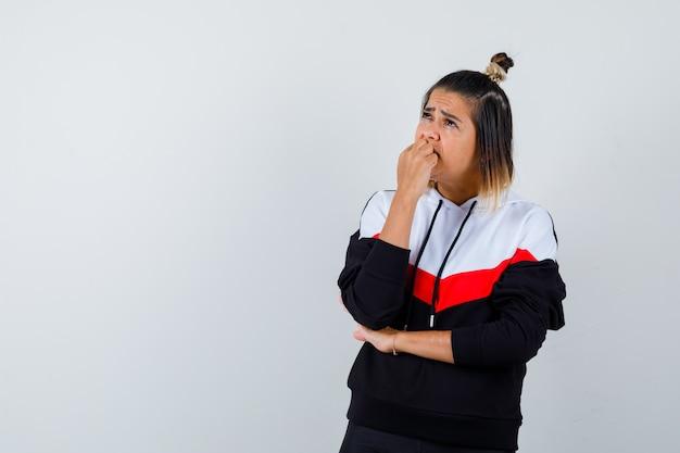 Jonge dame in hoodie trui met vuist op mond en teleurgesteld kijken