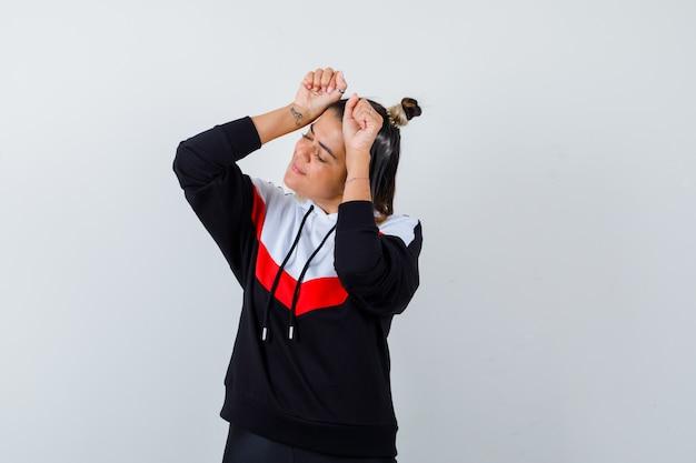 Jonge dame in hoodietrui die winnaargebaar toont en er gelukkig uitziet