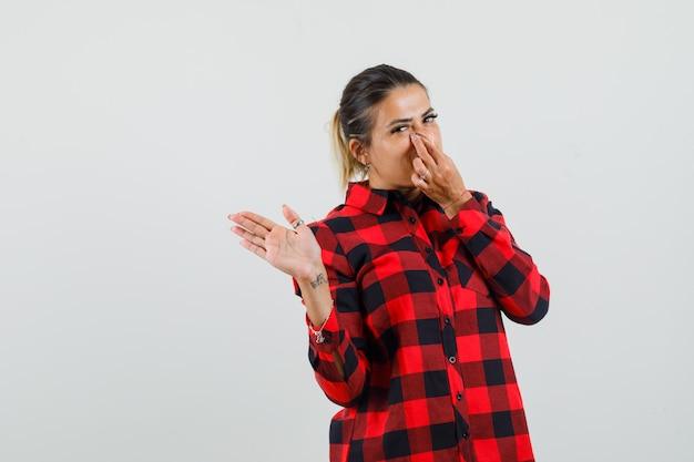 Jonge dame in ingecheckte overhemd neus knijpen vanwege slechte geur en ongemakkelijk op zoek
