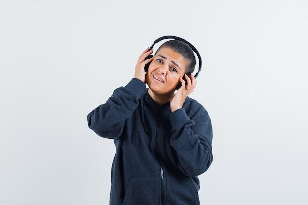 Jonge dame in jas hand in hand op oortelefoons