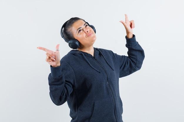 Jonge dame in jas luisteren muziek op oortelefoons tijdens het dansen en kijken geamuseerd