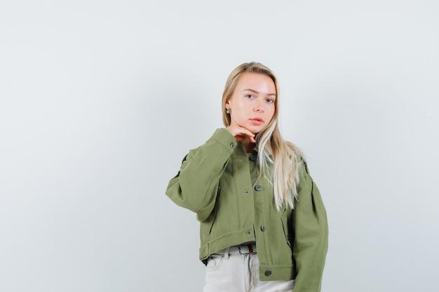 Jonge dame in jasje, broek die hand onder kin houdt en schattig, vooraanzicht kijkt.