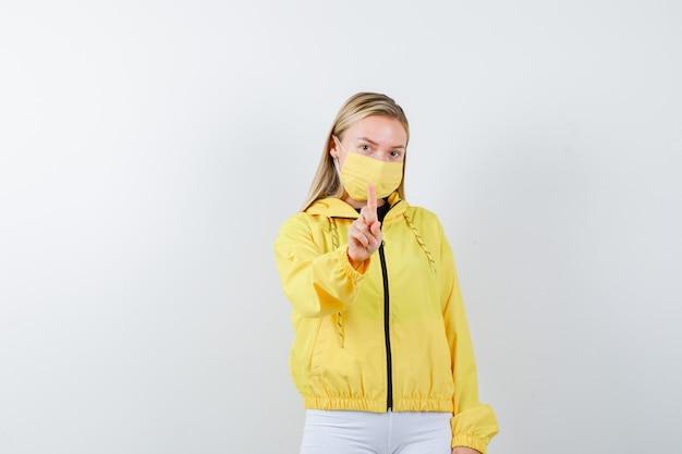 Jonge dame in jasje, broek, masker dat een minuutgebaar vasthoudt en er verstandig uitziet, vooraanzicht.