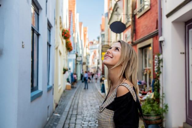 Jonge dame in jurk op middeleeuwse straat van bremen